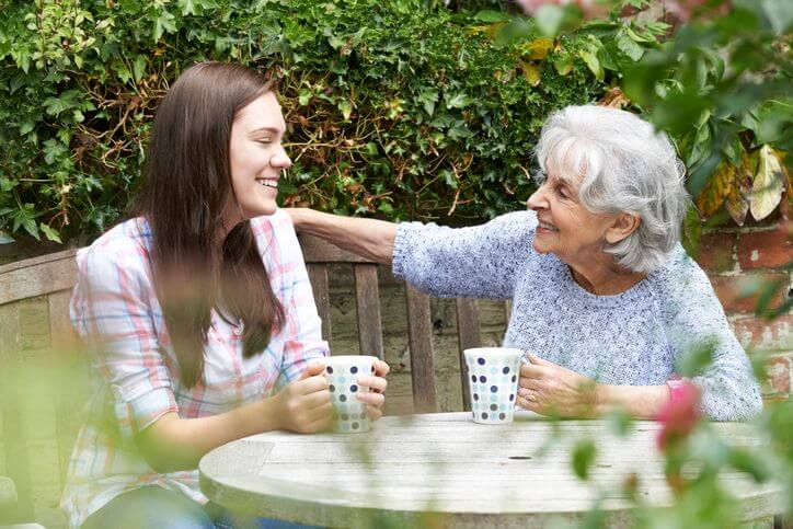 female social support worker drinking tea with senior client
