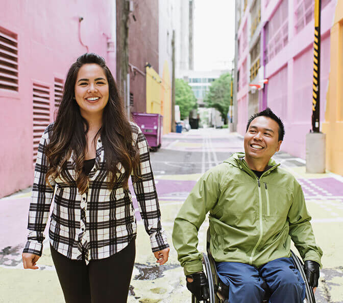 female support worker travelling with man with disability wheelchair